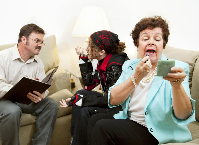 Family Counseling - Neglectful. Vain disinterested mother puts on makeup while her troubled teen daughter talks to a counselor stock photo