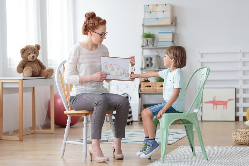 Family counselor helping young child. Professional family counselor helping young child to cope with his parents` divorce, showing him a drawing of a house royalty free stock images