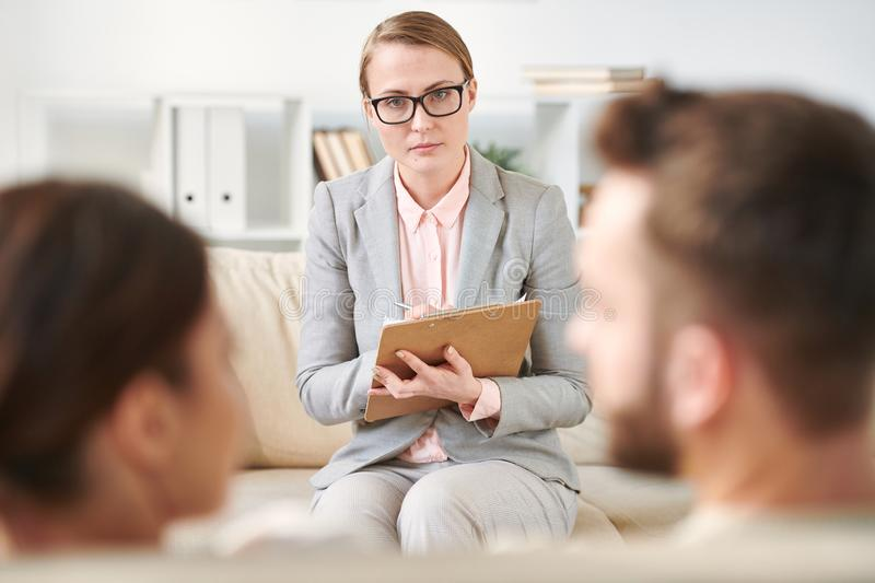 Family counselor. Young serious family psychotherapist with document making notes while listening to spouses at session royalty free stock images