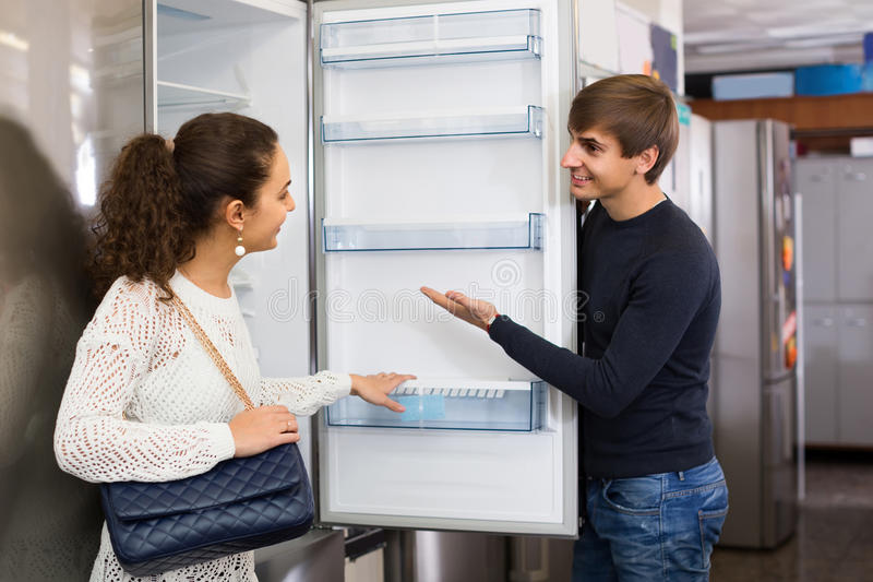 Family couple choosing new refrigerator in hypermarket. Middle class family couple choosing new refrigerator in hypermarket stock image