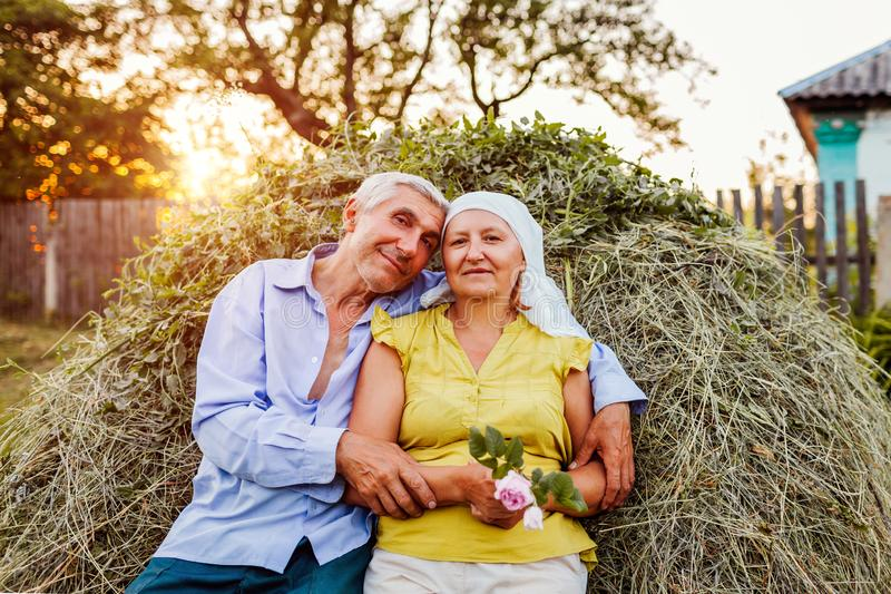 Family couple of farmers sitting on haystack and relaxing at sunset in countryside. Hard-working people hugging royalty free stock photography