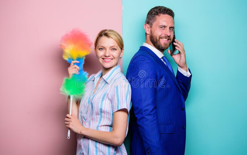 Family couple. Housewife and businessman. Career and housekeeping. Wife stand with dust brush husband has phone royalty free stock photography