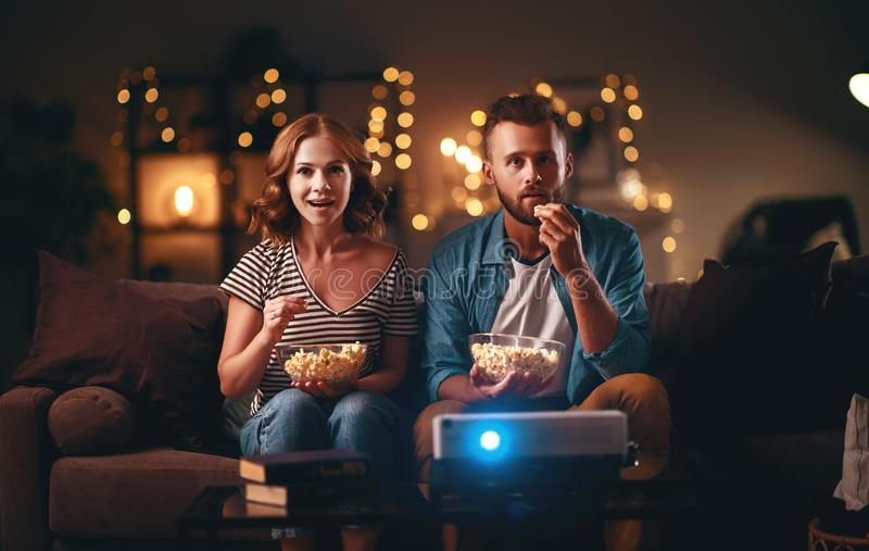 Family couple watching television projector at home on sofa. Family couple watching television projector at home on the sofa royalty free stock photo