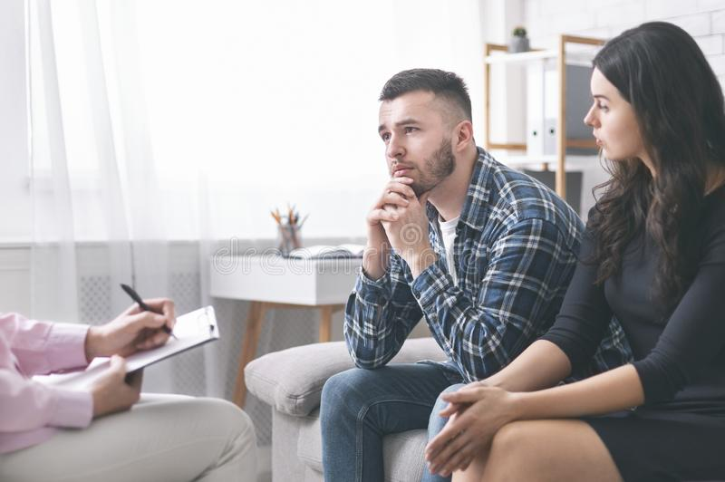 Young grumpy couple at marital counseling therapy stock photography