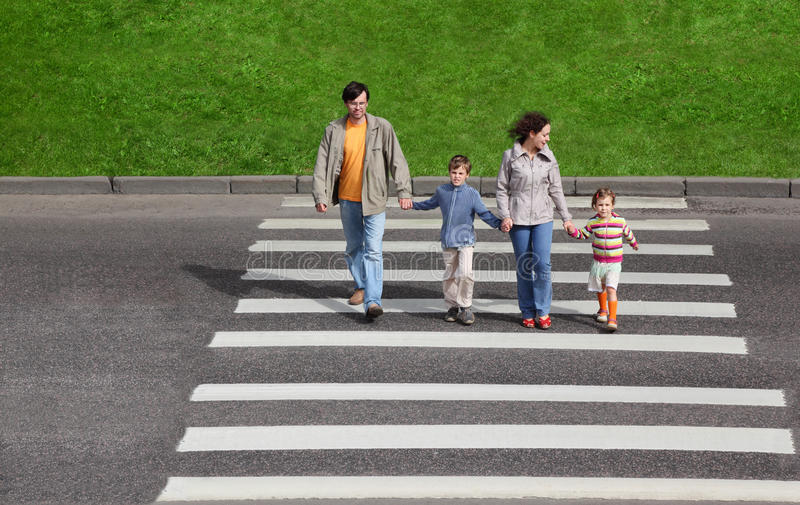 Family and crossing road, green fence and grass royalty free stock photography