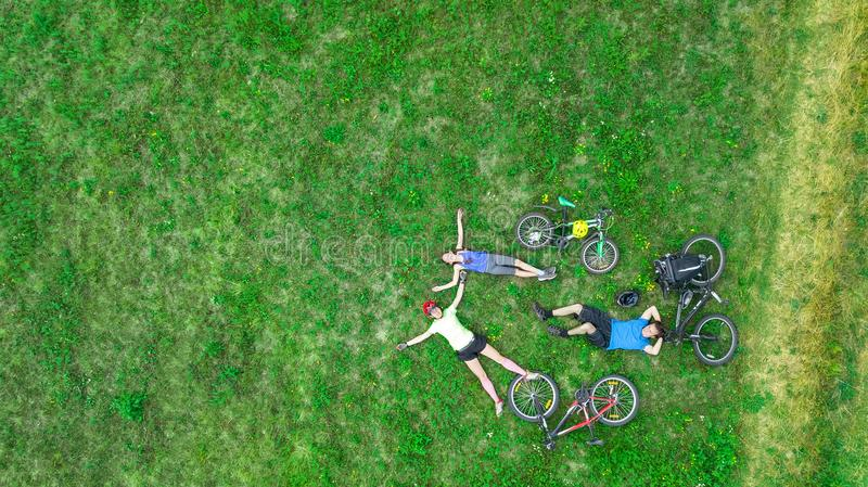 Family cycling on bikes outdoors aerial view from above, happy active parents with child have fun and relax on grass. Family sport and fitness on weekend royalty free stock photos