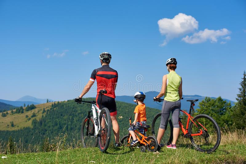 Family cyclists, mother, father and kid resting with bikes on top of grassy hill stock image