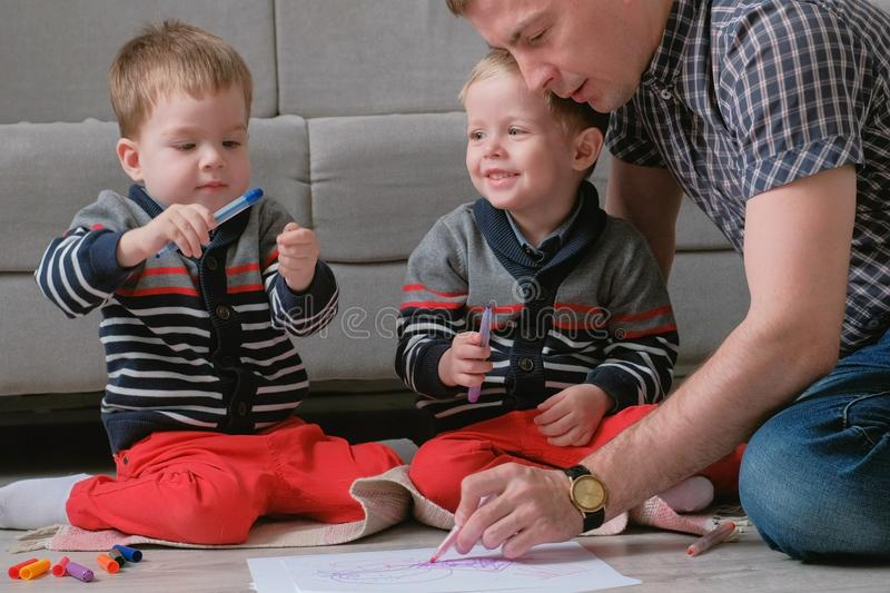 Family dad and two twin brothers draw together markers and felt pens sitting on the floor. stock photos
