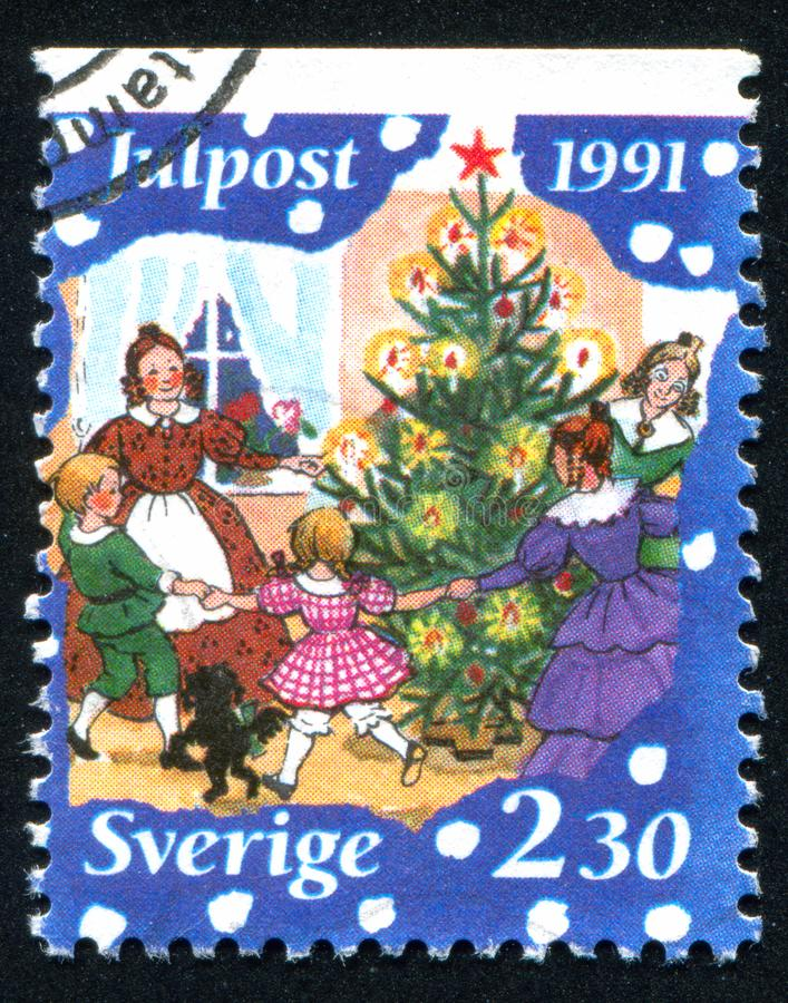 Family dancing around Christmas tree. SWEDEN - CIRCA 1991: stamp printed by Sweden, shows Family dancing around Christmas tree, circa 1991 stock images