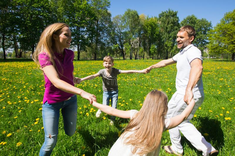Family dancing in park. Happy family of parents and children dancing in park holding hands royalty free stock photo