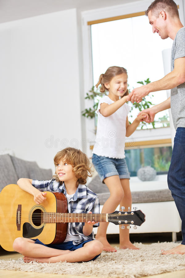 Family dancing and playing guitar. Happy family dancing to music from boy playing guitar stock images