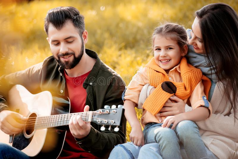 Family with daughter relaxing on a grassy hill while father playing. The guitar stock images