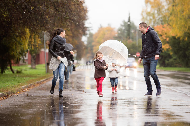 Family with daughters under the umbrellas, running. Rainy day. royalty free stock photos