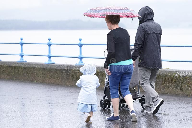 Family day out with umbrella wet weather British summer stock photography