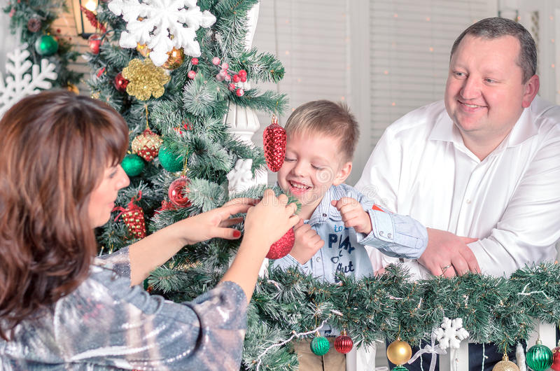 Family decorating a Christmas tree with boubles in the living-room stock images