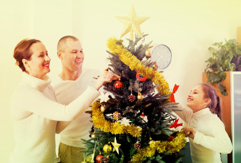 Family decorating Christmas tree stock images