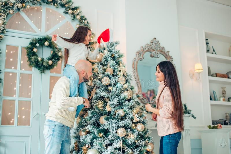 Happy family decorating a Christmas tree with boubles in the living-room royalty free stock photos