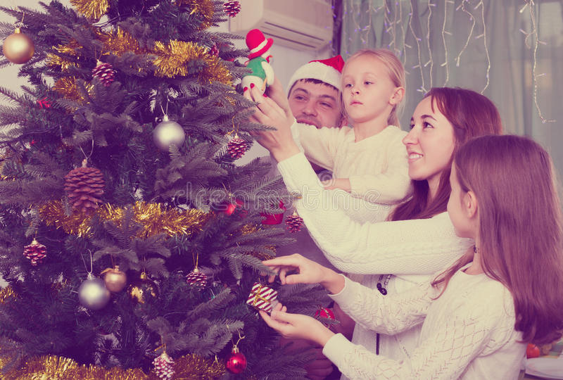 Family decorating Christmas tree at home royalty free stock photography