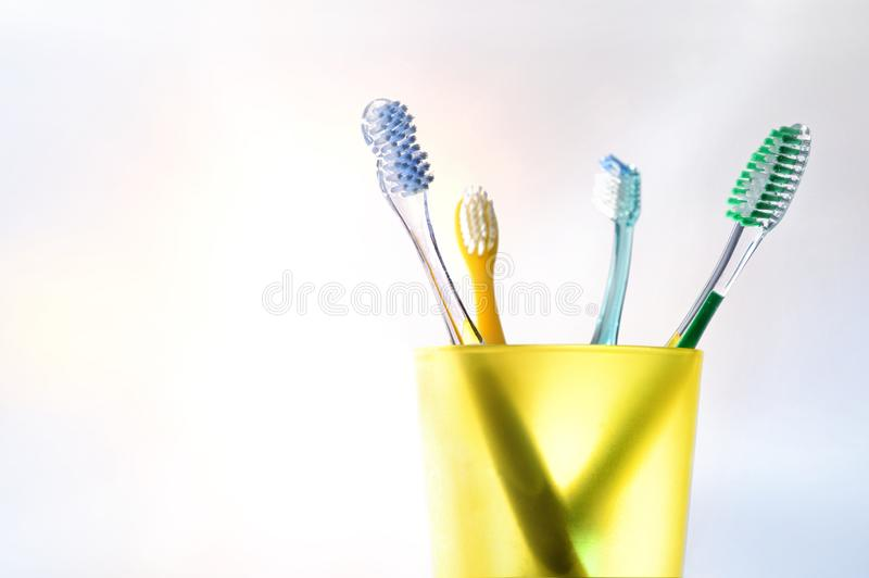 Daily family dental cleaning with yellow plastic cup with toothbrushes royalty free stock photo