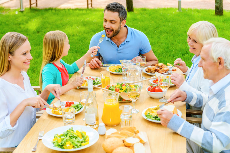 Family dining together. Top view of happy family of five people communicating and enjoying meal together while sitting at the dining table outdoors royalty free stock photos