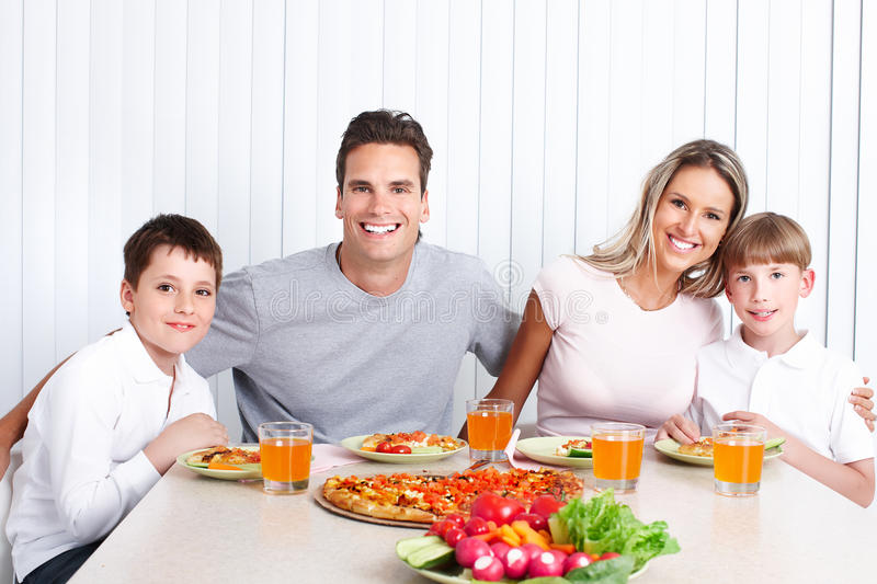 Family dinner. Father, mother and children eating a big pizza stock photo