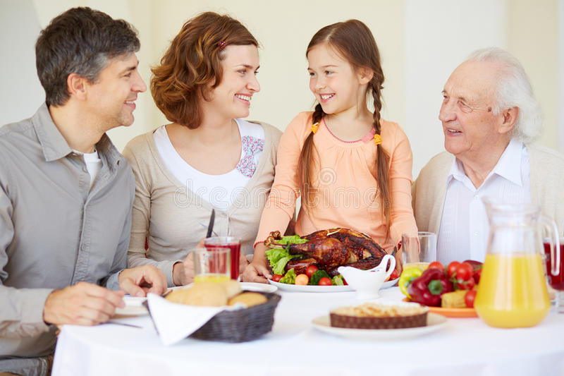 Family dinner. Portrait of happy family members looking at cute girl by Thanksgiving table royalty free stock photography