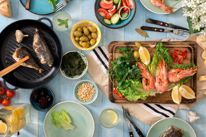 Family dinner table with shrimp, fish grilled, salad, snacks, le royalty free stock photography