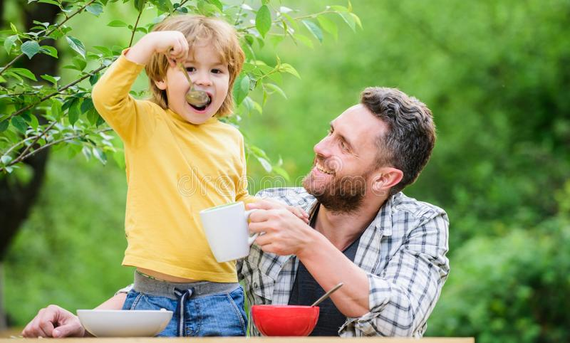 Family dinner time. father and son eating outdoor. happy fathers day. Little boy with dad eat cereal. Morning breakfast stock images