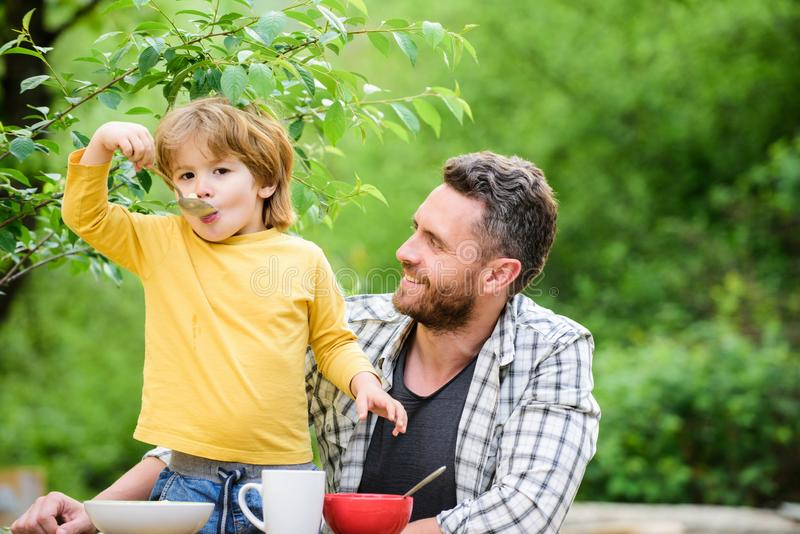 Family dinner time. happy fathers day. Little boy with dad eat cereal. summer picnic. Morning breakfast. healthy food. And dieting. Childrens day. father and royalty free stock photos