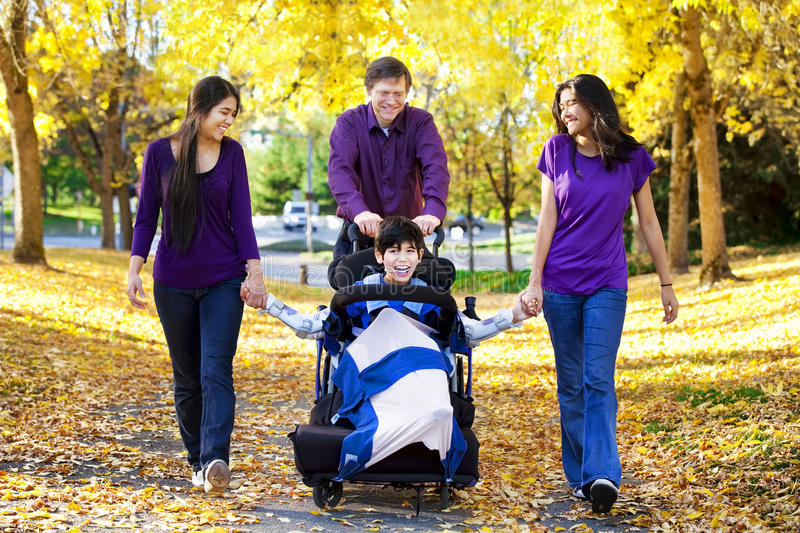 Family with disabled child in wheelchair walking among autumn le royalty free stock image
