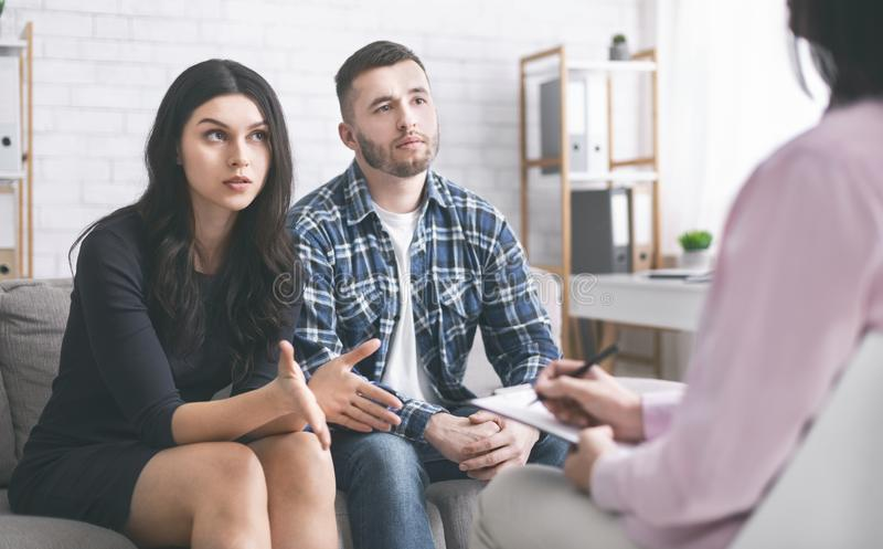 Young couple discussing their problems at marital therapy. Family disagreement. Young couple discussing their problems at marital therapy with psychologist royalty free stock image