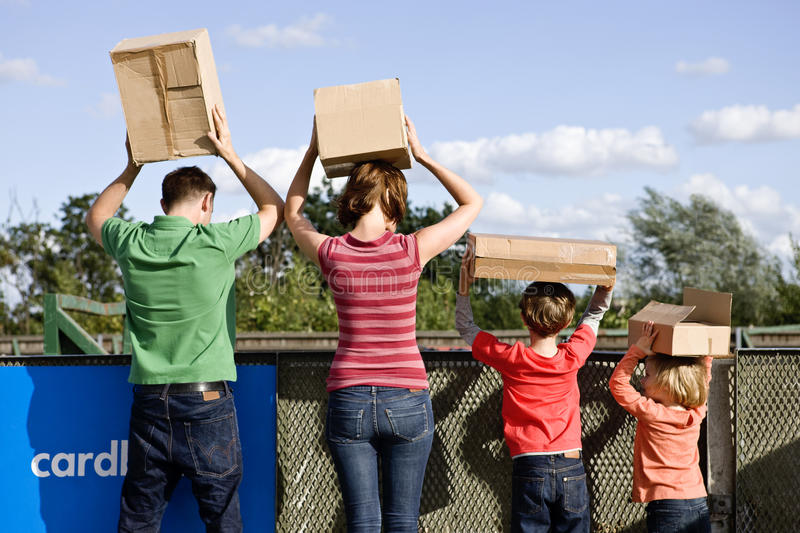 A family disposing of cardboard boxes at a recycling centre, rear view stock images