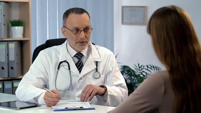 Family doctor listening to patient, filling out medical insurance, health care royalty free stock photos