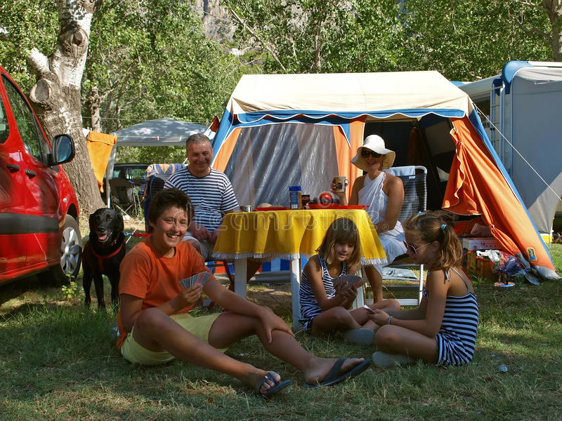 Family with dog at a camp. Happy smiling family (mother and father with three children) with dog (black labrador) full enjoy - spending summer vacation at a camp