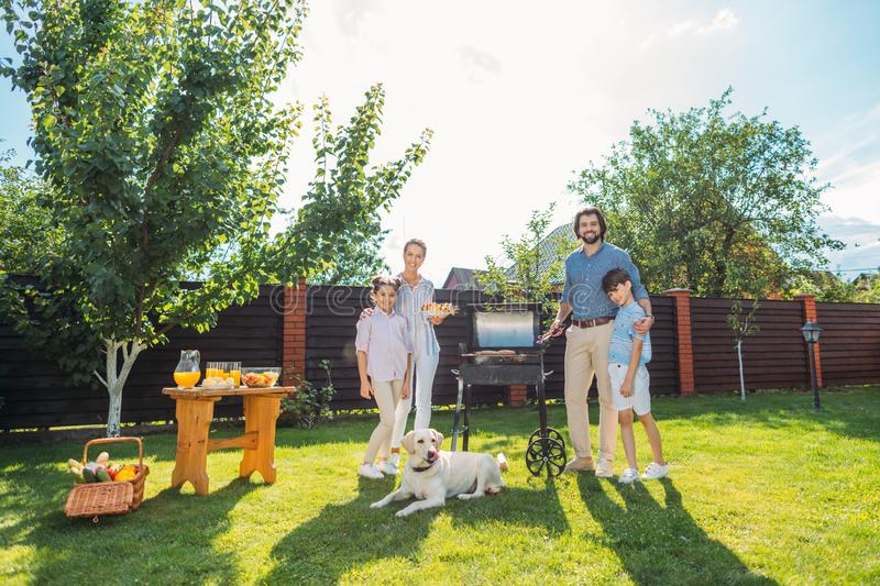 Family with dog having barbecue together on backyard. On summer day stock image