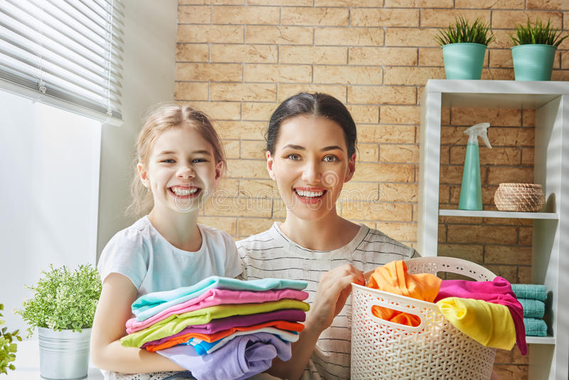 Family doing laundry at home. Beautiful young women and child girl little helper are having fun and smiling while doing laundry at home royalty free stock photography