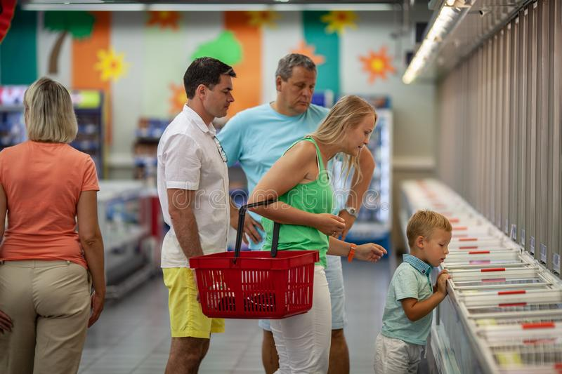 Family doing the shopping in the supermarket. Big family with parents, grandparents and child shopping for food in the supermarket. Little boy exploring the royalty free stock images