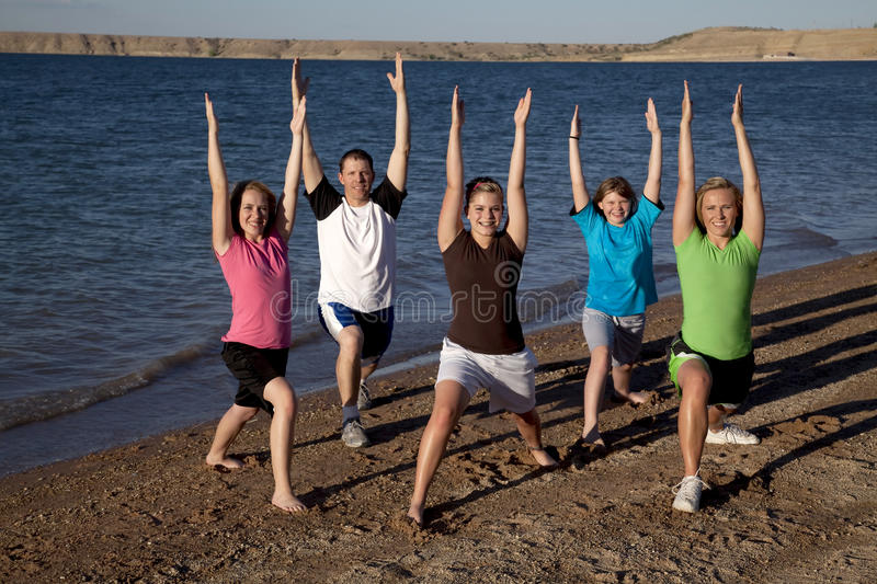 Family doing yoga. A family doing a yoga stretch on the beach by the water stock photography