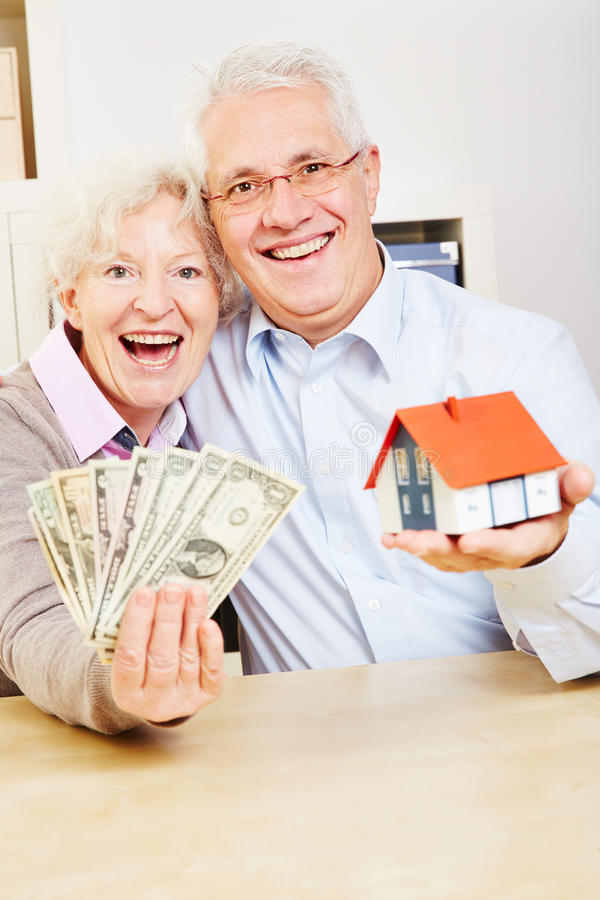 Family with dollar and small house. Happy elderly family with dollar bills and a small house royalty free stock image