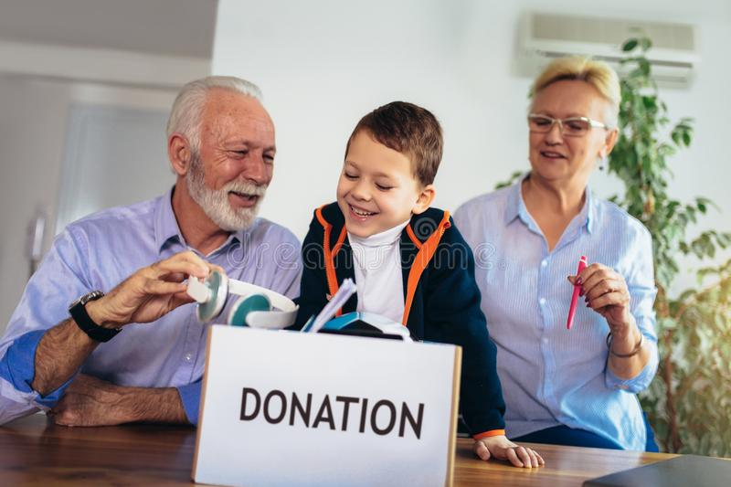 Family donating unwanted items. They are holding box with stuffs for donation stock photos