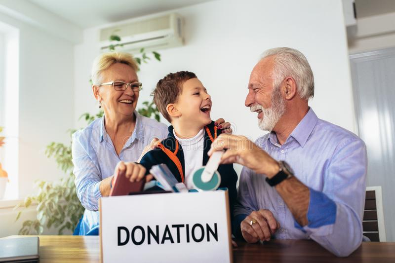 Family donating unwanted items. They are holding box with stuffs for donation royalty free stock images