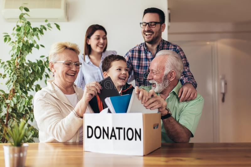 Family donating unwanted items. They are holding box with stuffs for donation stock image