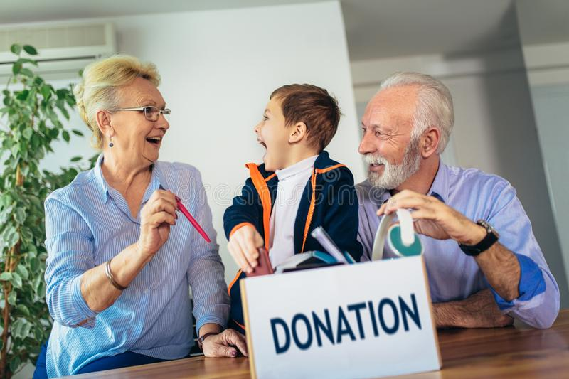 Family donating unwanted items. They are holding box with stuffs for donation stock photography