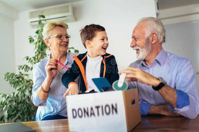 Family donating unwanted items. They are holding box with stuffs for donation royalty free stock photography