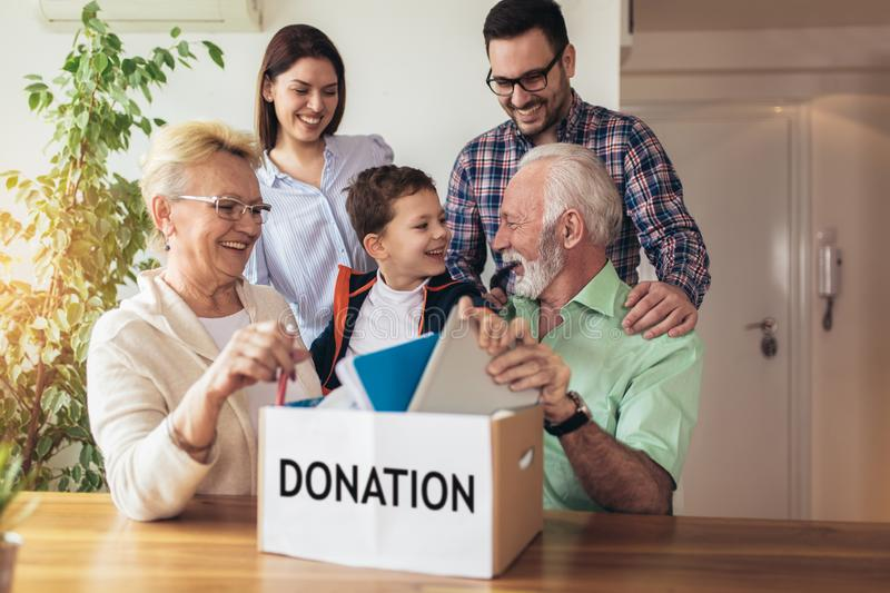 Family donating unwanted items. They are holding box with stuffs for donation stock images