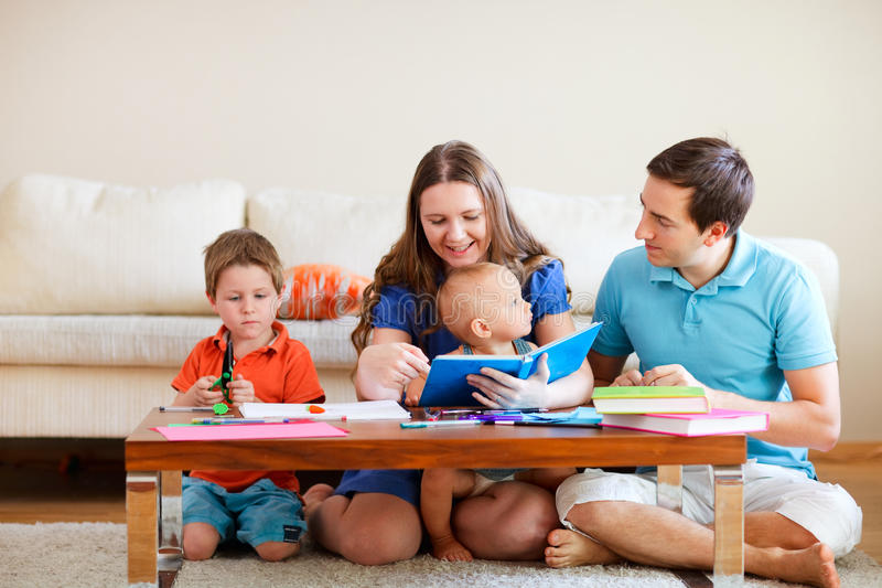 Family drawing. Young family with two kids drawing and reading together royalty free stock photo