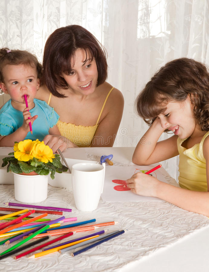 Family drawing. Two little girls making a drawing for their mother stock photos