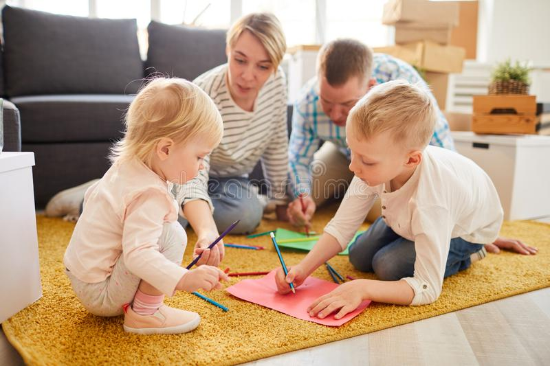 Family drawing house of dream. Group of concentrated family members sitting on soft carpet and drawing house of dream while planning moving together royalty free stock photo