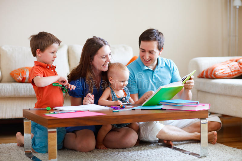 Family drawing and reading. Young happy family with two kids drawing and reading together stock photos