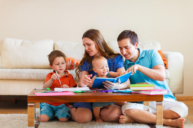 Family drawing. Young family with two kids drawing and reading together stock photos